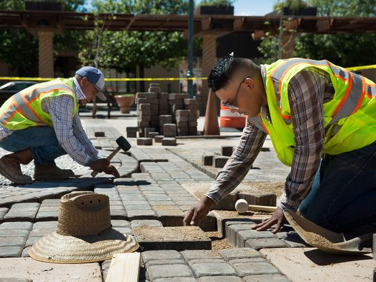"Employees of Landscape and Design Center Adrian Sierra, right, and Adolfo Rios place pavers around artist Tony Pennock's ""Rio Grande Time"" sun dial on Friday, Sept. 9, 2016, at the Plaza de Las Cruces. The official plaza opening is scheduled for Saturday, Sept. 17, 2016. (Photo: Anayssa Vasquez/Sun-News)"